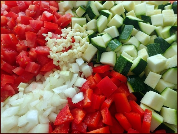 Ingredients for zucchini ratatouille: Tomatoes, red bell peppers, onions, garlic, and zucchini.