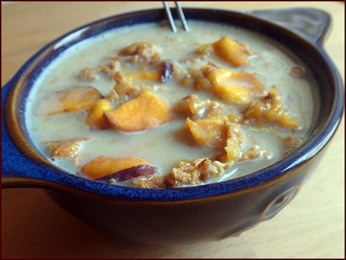 A healthy bowl of peach crunch breakfast with milk.